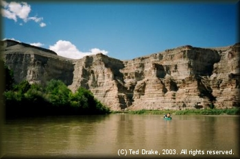 Tall sandstone canyon walls give perspective to the Green River