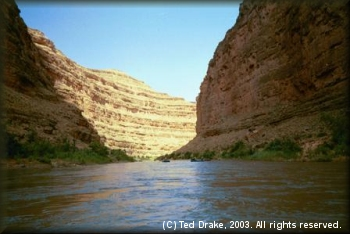 A setting sun casts shadows and color hues along the canyon walls